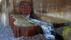Aguas residuales que salen a raudales del tubo oxidado viejo del drenaje en la costa de mar almacen de metraje de vídeo