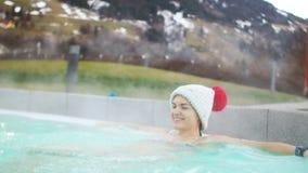 Aguas termales en las montañas Mujer que descansa en aguas termales en invierno almacen de video