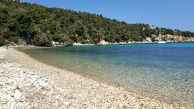 Aguas y guijarros cristalinos en la playa, islas de Grecia imagen de archivo