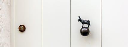 Agudamente a porta de madeira branca com asno deu forma ao botão de porta de bronze fotografia de stock royalty free
