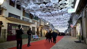 White umbrellas iluminated by Christmas lights. AGUEDA, PORTUGAL - CIRCA DECEMBER 2018: The beauty of white umbrellas illuminated by Christmas lights decorating stock video