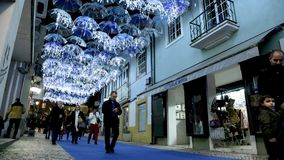 White umbrellas iluminated by Christmas lights. AGUEDA, PORTUGAL - CIRCA DECEMBER 2018: The beauty of white umbrellas illuminated by Christmas lights decorating stock video footage