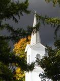Aguja blanca de la iglesia iluminada por el eje de la luz Imagen de archivo