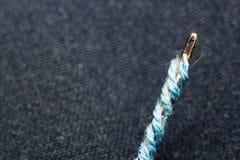 Aguja con el hilo azul en un fondo de la macro borrosa del tejido Fotos de archivo