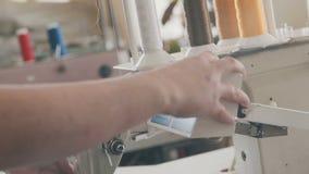 Aguja con el hilo Máquina del bordado en la camiseta en industria textil metrajes