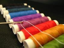 Aguja con la cuerda de rosca en fondo coloreado Foto de archivo
