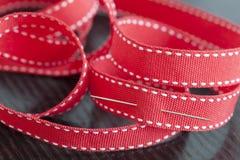 Aguja de costura en una cinta roja Fotos de archivo