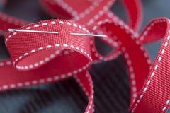 Aguja de costura en una cinta roja Foto de archivo