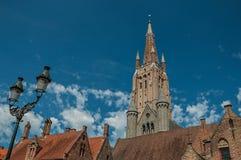 Aguja de la iglesia del ladrillo, tejados y lámpara pública poniendo en contraste con el cielo azul en Brujas Imágenes de archivo libres de regalías