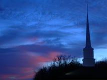 Aguja de la iglesia en la puesta del sol Fotografía de archivo libre de regalías