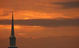 Aguja de la iglesia fijada contra puesta del sol Foto de archivo