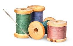 Aguja e hilo multicolor en el carrete de madera fotos de archivo