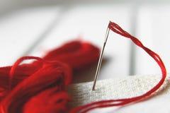 Aguja en lona con el hilo rojo para el bordado Cierre de la macro del bordado para arriba Fotografía de archivo libre de regalías
