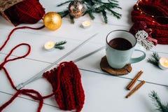 Agujas que hacen punto, café y velas, puntillas del abeto y luces de la Navidad en el fondo blanco Imágenes de archivo libres de regalías