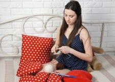 Agujas que hacen punto de la costurera atractiva de la muchacha Foto de archivo