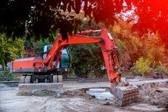 agujero de excavación del excavador, rompiendo el asfalto de la calle, reparando el tubo dañado del abastecimiento de agua Imagen de archivo
