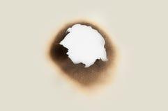 Agujero de la quemadura en un papel imagenes de archivo