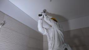 Agujero de perforación del trabajador manual en el cartón yeso del techo para el montaje de iluminación llevado almacen de metraje de vídeo