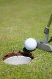 Agujero del golf con la bola y el putt Foto de archivo libre de regalías