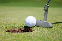 Agujero del golf con la bola y el putt Imagen de archivo