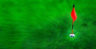 Agujero del golf en hierba verde con la bandera roja Imagen de archivo libre de regalías