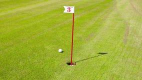 Agujero en campo de golf con el número 3 y la bola almacen de video