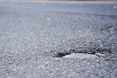 Agujero en la calle gris del asfalto imagen de archivo