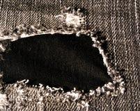 Agujero en pantalones vaqueros gastados Imágenes de archivo libres de regalías
