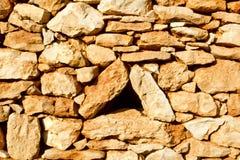 Agujero envejecido de la ventana del triángulo de la pared de piedra de la albañilería Imagenes de archivo
