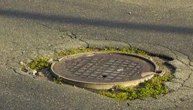 Agujero grande en asfalto y la cubierta de boca circular de las aguas residuales bien en camino, Fotografía de archivo libre de regalías