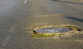 Agujero grande en asfalto y la cubierta de boca circular de las aguas residuales bien en camino, Foto de archivo libre de regalías