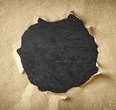 Agujero hecho del papel rasgado sobre fondo negro texturizado Imagen de archivo libre de regalías