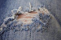 Agujero rasgado en textura azul del dril de algodón Foto de archivo