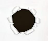 Agujero redondo en documento sobre fondo negro Imagenes de archivo