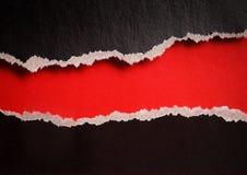 Agujero rojo con los bordes rasgados en papel negro Foto de archivo