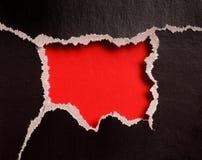 Agujero rojo con los bordes rasgados en papel negro Fotografía de archivo libre de regalías