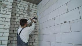 Agujeros de perforación del constructor en pared aireada del bloque de cemento con el taladro eléctrico almacen de metraje de vídeo