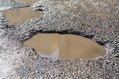 Agujeros en la carretera de asfalto llenada de agua Imagen de archivo