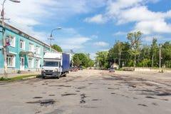 Agujeros y grietas en la carretera nacional del asfalto en el pequeño pueblo ruso Foto de archivo