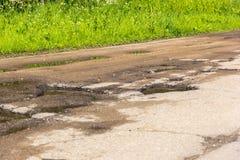 Agujeros y grietas en la carretera nacional del asfalto en el pequeño pueblo ruso Fotografía de archivo libre de regalías