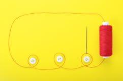 Agulha com os botões vermelhos da linha e da roupa Foto de Stock Royalty Free