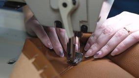 agulha da m?quina de costura no movimento uma costureira costura o couro preto em uma oficina costurando Agulhas da m?quina de co vídeos de arquivo