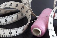 Agulha de medição da fita e de costura em um carretel da linha fotografia de stock