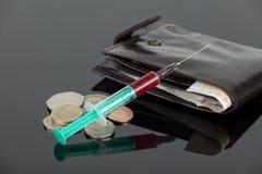 Agulha hipodérmica enchida sangue que coloca através de algum dinheiro Fotografia de Stock