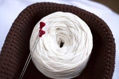 Agulhas de confecção de malhas com corações vermelhos, bola branca do fio da fita Fotos de Stock