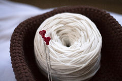 Agulhas de confecção de malhas com corações vermelhos, bola branca do fio da fita Foto de Stock Royalty Free