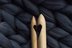 Agulhas de confecção de malhas de madeira no fundo do blanke cinzento de lãs do merino imagens de stock