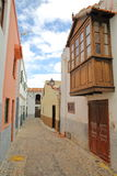AGULO, LA GOMERA, SPAIN: Cobbled street with colorful facades and a wooden balcony Royalty Free Stock Photography