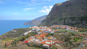 AGULO, LA GOMERA, SPAIN: General view of the village with terraced fields and cliffs in the background. General view of the village with terraced fields and royalty free stock photo