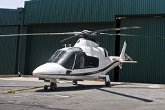 Agusta A109 Helicopter. Helicopter parked outside airport hangars Royalty Free Stock Images